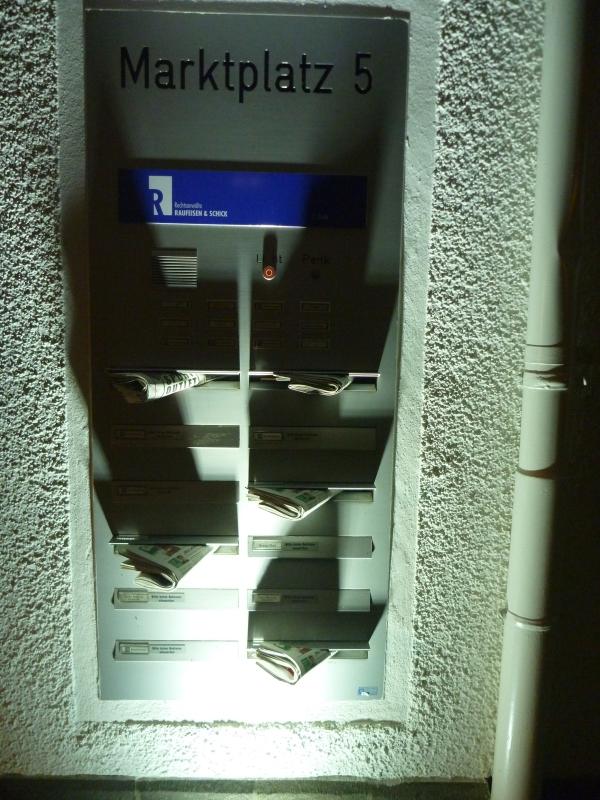 Briefkasten mit eingesteckten Zeitungen - diese werden von einem Boden-Einbau-Strahler angeleuchtet und werfen interessante Schatten